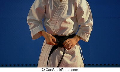 Close up of man tying up knot of black belt on special karate kimono equipment in slow motion