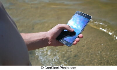 Close up of man using his smart phone at the beach