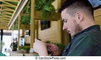 Close up of man using smartphone in cafe