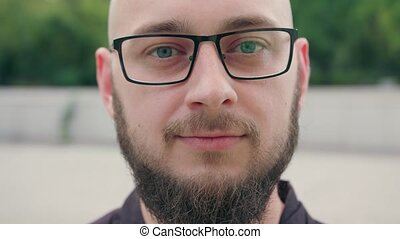 Close-up of Man with Beard wearing Glasses in Town - A man...