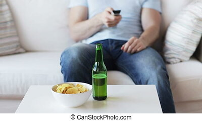 close up of man with beer and remote at home - drinks,...