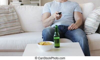 close up of man with beer and remote at home