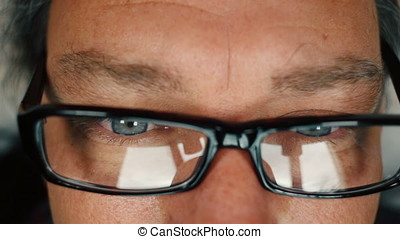 Close up of man with blue eyes reading and taking off eyeglasses to rub his eyes