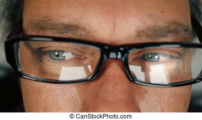 Close up of man with blue eyes working on computer and...