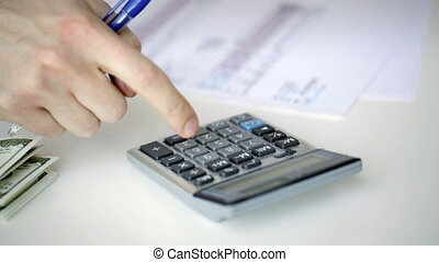 close up of man with calculator counting money