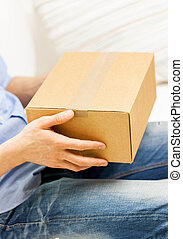 close up of man with cardboard box parcel at home