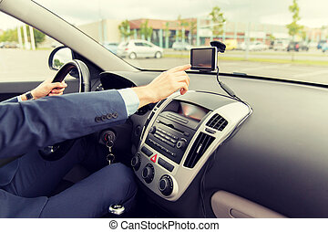 close up of man with gps navigator driving car - transport,...