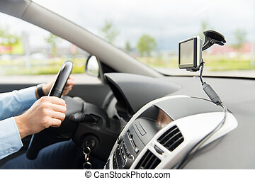 close up of man with gps navigator driving car - transport,...