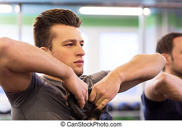 close up of man with kettlebell exercising in gym