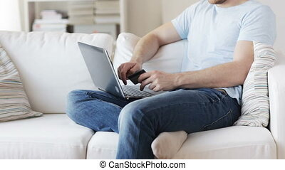 close up of man with laptop and credit card