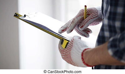 repair, building, construction and people concept - close up of man with measuring ruler taking notes to clipboard