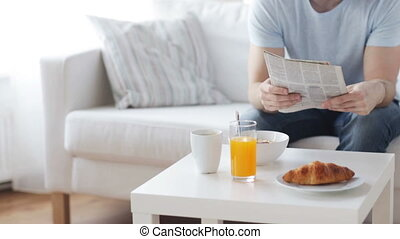 close up of man with newspaper having breakfast