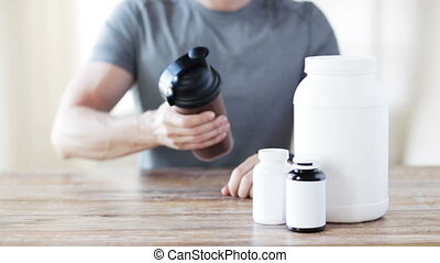 close up of man with protein shake bottle and jars - sport,...