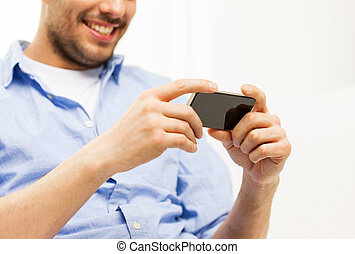 close up of man with smartphone at home