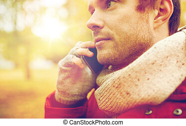 close up of man with smartphone calling in autumn