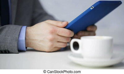 close up of man with tablet pc drinking coffee