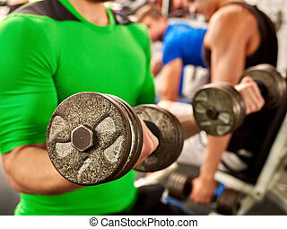 Close up of man working his arms with dumbbells at gym.