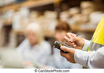 Close up of manager wearing yellow vest using handheld in a...