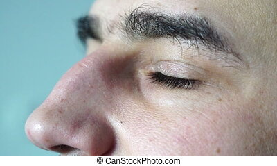 Close up of man's brown eyes looking upward opening and...