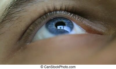 Close up of mans eye looking on computers monitor.
