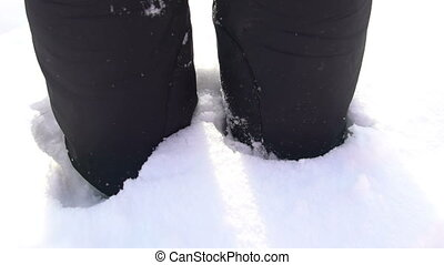 Close-up of man's feet walking on the mountains boots feet in snow. Slow-motion filming