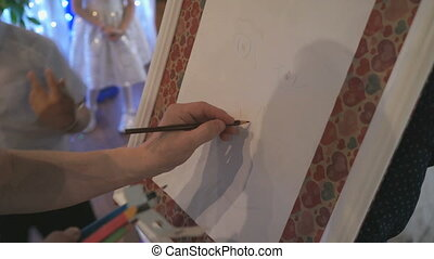 Close-up of man's hand drawing a face on the easel -...