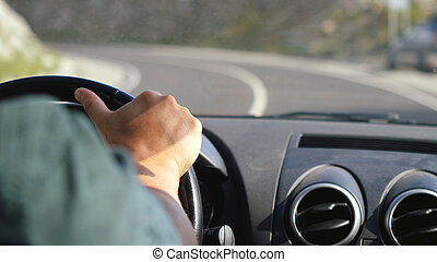 Close up of man's hand on the steering wheel driving a car in the long road along mountains