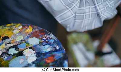 Close up of man's hand painting still life picture on canvas in art-school