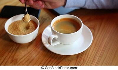 Close-up of man's hand pours sugar into a cup of coffee at the bar, and stir it