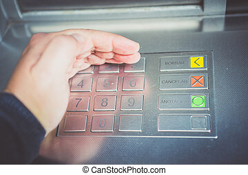 Close-up of man's hand pushing button on atm machine