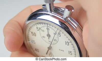 Close up of man's hand starting up a stopwatch at white...