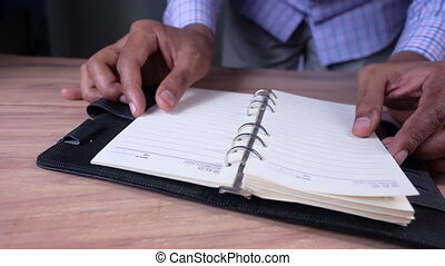 Close up of man's hand turning a pager of a diary