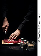 Close up of mans hands chopping meat in restaurant
