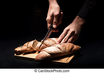 Close up of mans hands chopping the baguette