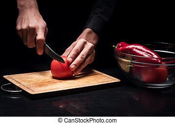 Close up of mans hands chopping tomato