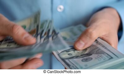 Close-up of man's hands counting hundred dollar bills. Slow motion