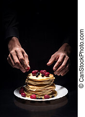 Close up of mans hands decorating the pancakes