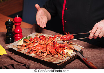 Close up of mans hands demonstrating crayfishes in restaurant