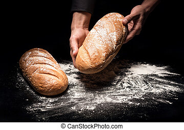 Close up of mans hands holding a bread