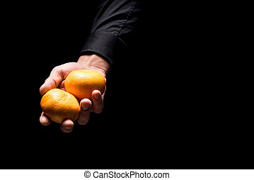 Close up of mans hands holding tangerines