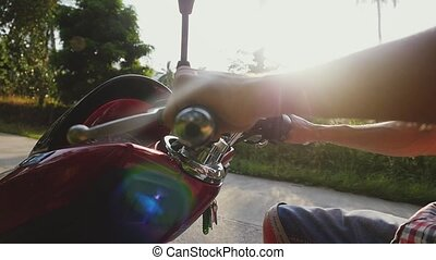 Close up of man's hands on the wheel of a motorcycle traveler driving motorbike on tropical sunny road through the sun with beautiful lens flare effects in a jungle. slow motion. Close up. 1920x1080