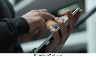 Close-up of man's hands typing something on the tablet