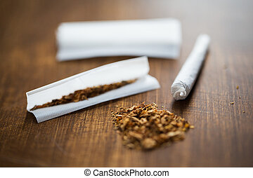 close up of marijuana joint and tobacco - drug use,...