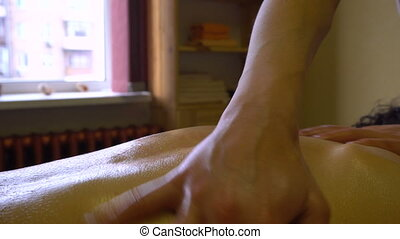Close up of Masseur Woman Makes Massage with Warm Oil to a Young Man