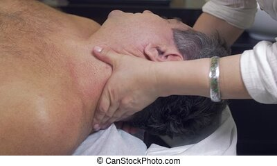 Close up of masseuse hands make therapeutic massage of head...