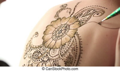 Close-up of master creates mehendi on body, isolated over...