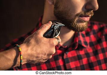 Close-up of Master cuts hair and beard of men