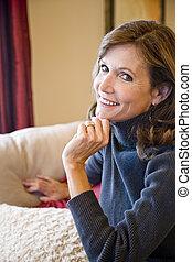 Close up of mature woman sitting on sofa
