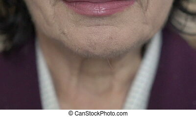 Close up of mature woman's neck, lips, smiling. Slowly