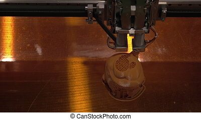 Close-up of mechanism of 3D printer working on printing plastic toys